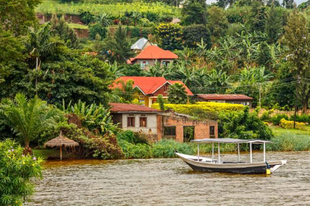 Dachboot an der Küste mit ruanschem Dorf im Hintergrund, Kivu See, Ruanda – Foto