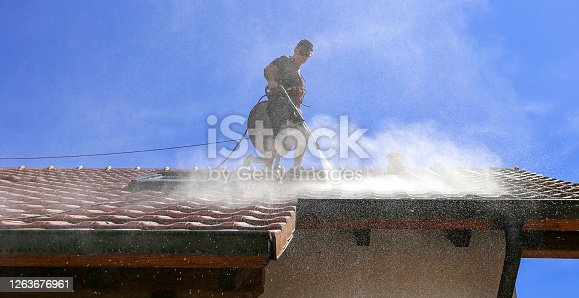 Workers cleaning the roof of moss and dirt with a high pressure cleaner. Secured with a safety rope.