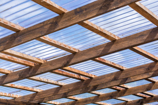 Roof construction of a self-made carport made of wooden beams and transparent roof panels stock photo