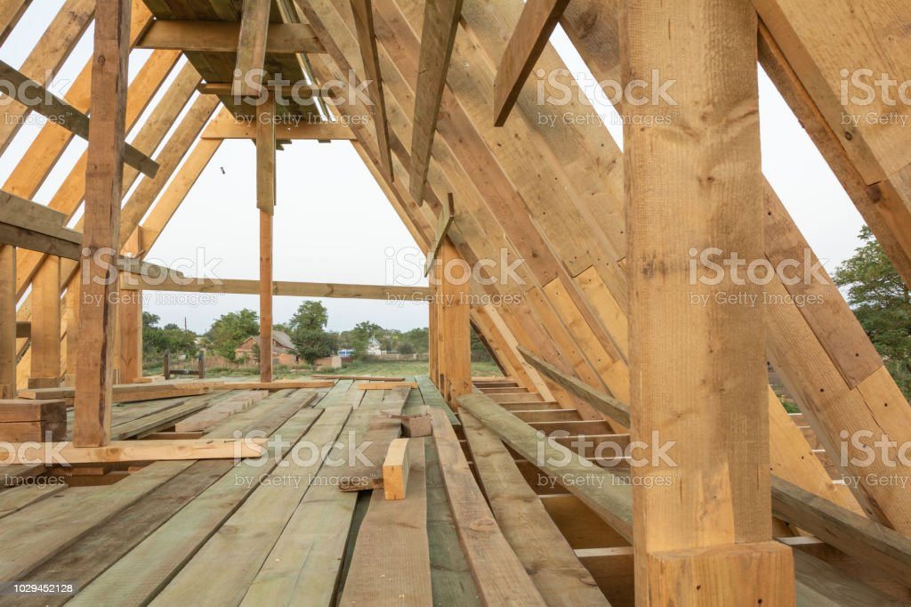 Roof frame structure in wood frame home under construction at sunset,...