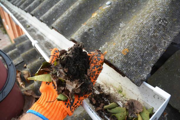 Dakgoot die met hand van gevallen bladeren schoonmaakt. foto