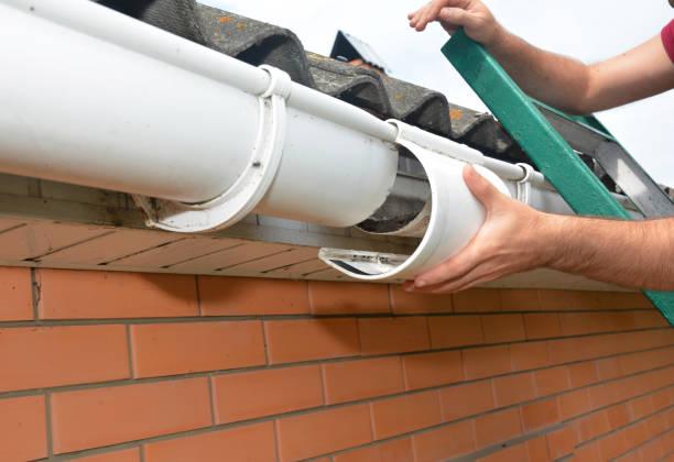 Dakgoot reparatie. Reparatie van guttering. Roofer aannemer reparatie huis regengoot pijpleiding. foto
