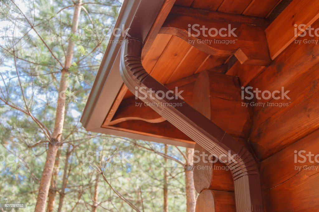 Roof gutter system on log house in forest stock photo