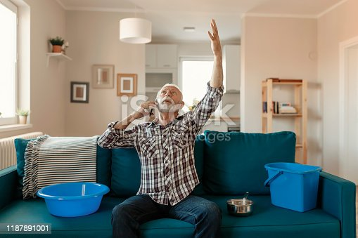 Angry Bearded Senior Man Talking on Smartphone Near Plastic Wash Bowl at Home in the Living Room Because of Roof Leaking