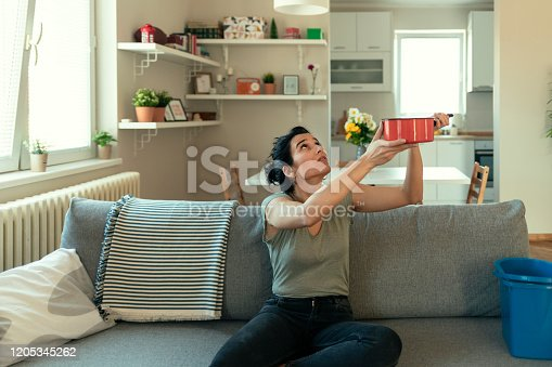 Shocked  Woman Looks at the Ceiling While Collecting Water Which Leaks in the Living Room at Home. Worried Woman Holding Bucket While Water Droplets Leak From Ceiling in Living Room