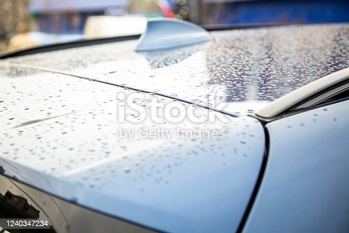 881639308 istock photo roof of a blue car with a fin antenna of a radio receiver covered with raindrops after rain. closeup, soft focus. blur background 1240347234