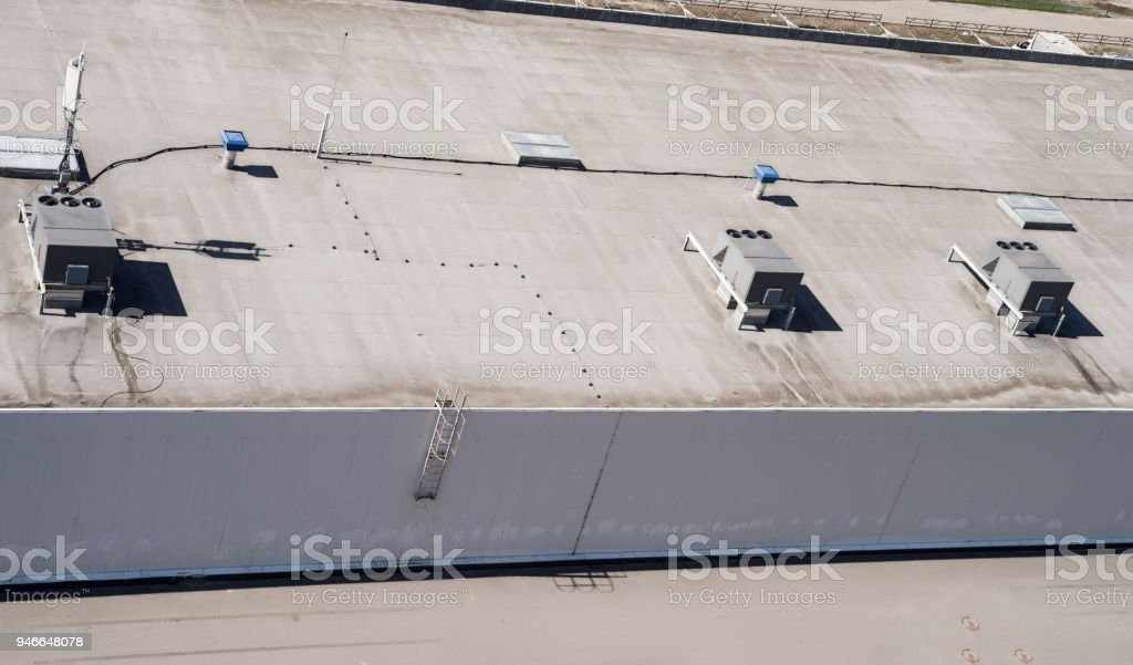 A roof of a commercial building with a external units of the commercial air conditioning and ventilation systems stock photo