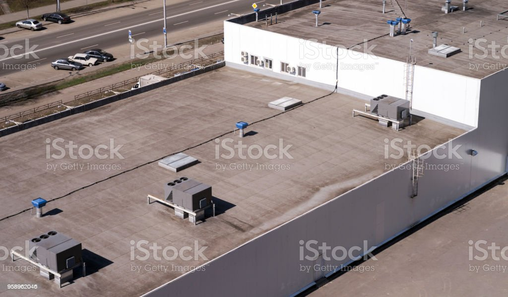Roof of a commercial building with a external units of the commercial air conditioning and ventilation systems stock photo