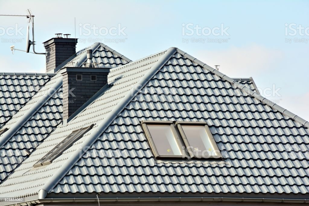 Roof of a detached house with a skylight and chimney against the sky stock photo