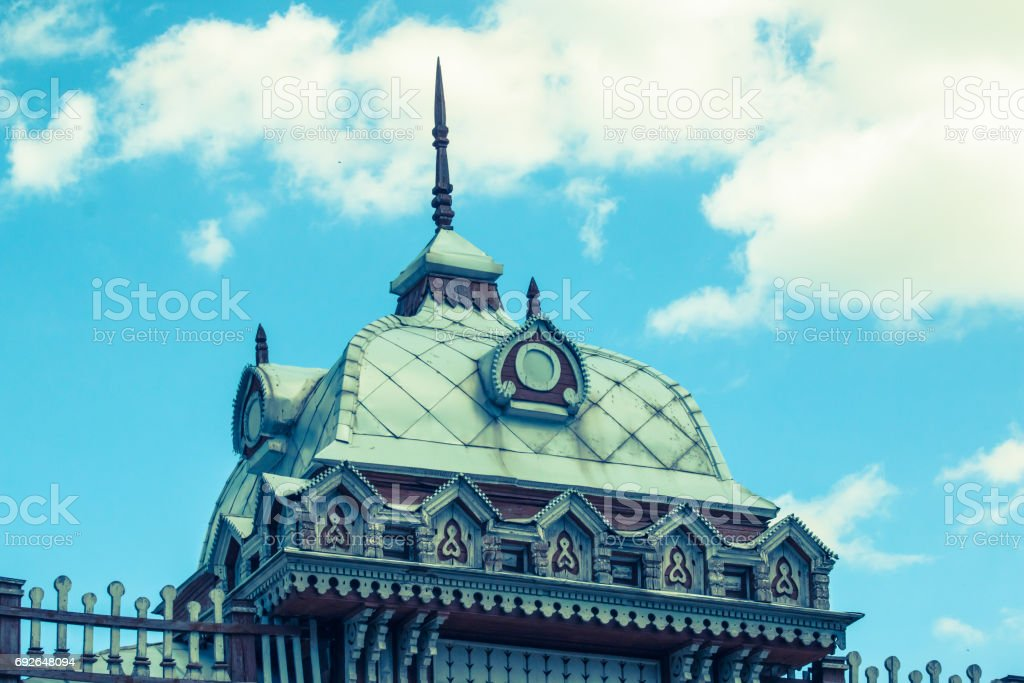 Roof of an ancient building with elements of wood carving on the sky background. stock photo