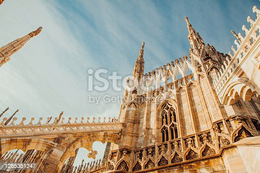 istock Roof of Milan Cathedral Duomo di Milano with Gothic spires and white marble statues. Top tourist attraction on piazza in Milan, Lombardia, Italy. Wide angle view of old Gothic architecture and art 1285351247