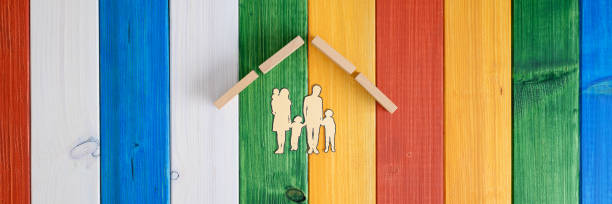 Roof over a paper cut silhouette of a family in a conceptual image stock photo