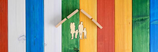Dach über einer papiergeschnittenen Silhouette einer Familie in einem konzeptuellen Bild – Foto