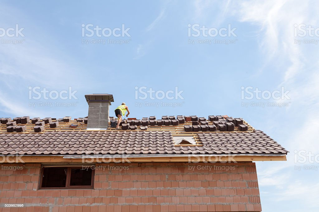 Roof renovation: installation of tar paper, new tiles and chimney stock photo