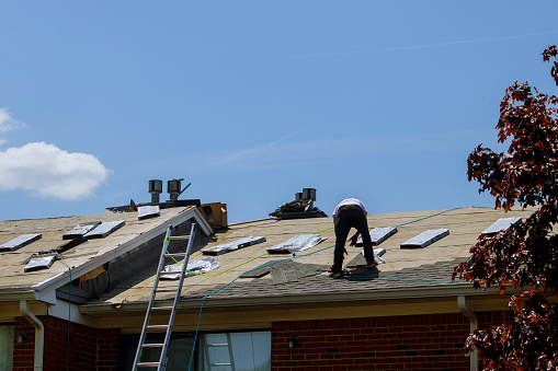 Roof repair, worker with replacing gray tiles shingles on house being applied