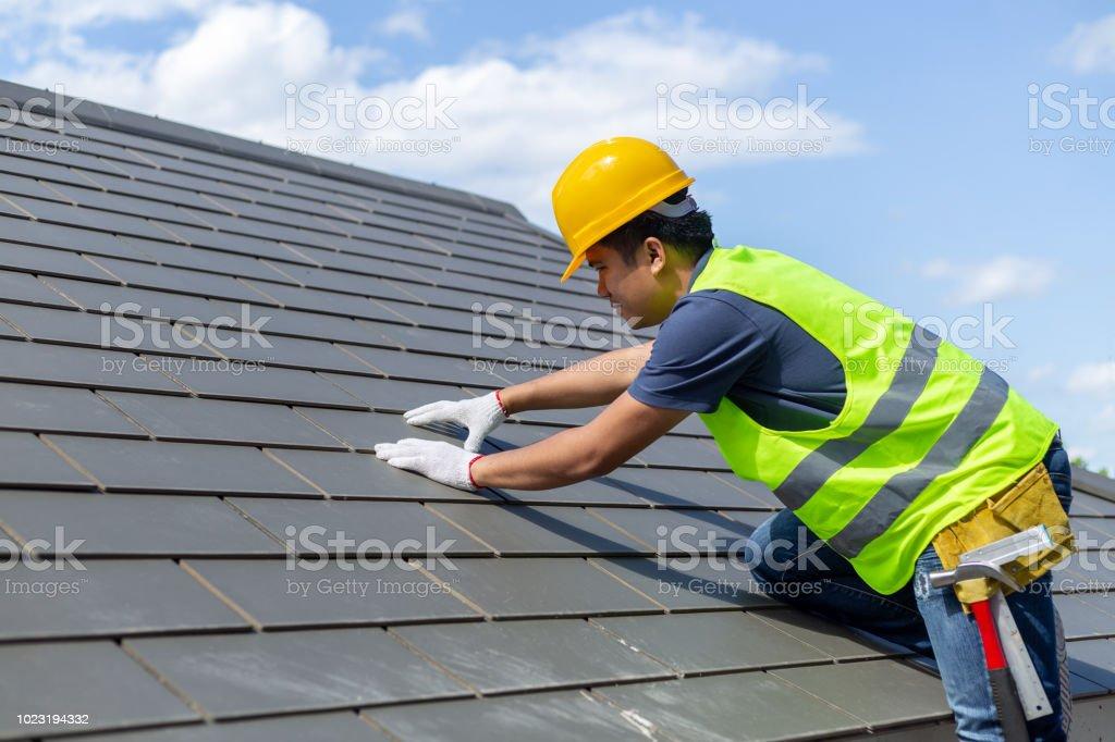 지붕 수리, 교체 회색 타일 또는 집에 대상 포진 배경 및 복사 공간으로 푸른 하늘 흰 장갑과 함께 노동자 지붕-지붕 타일 취재에 서 있는 건설 노동자. - 로열티 프리 DIY 스톡 사진