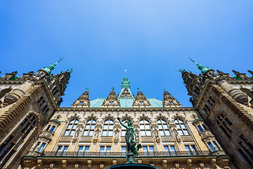 Roof shape view of the beautiful famous Hamburg town hall with Hygieia fountain from courtyard near market square and lake Binnenalster in Altstadt quarter, Hamburg, Germany
