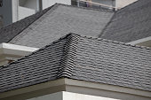 istock roof shingle background and texture. dark asphalt tiles on the roof. 1302078406