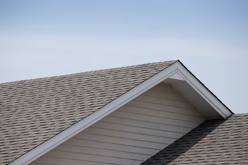 Roof shingles on top of the house against blue sky with cloud, dark asphalt tiles on the roof background
