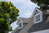 istock Roof shingles with garret house on top of the house among a lot of trees. dark asphalt tiles on the roof background. 1212371986