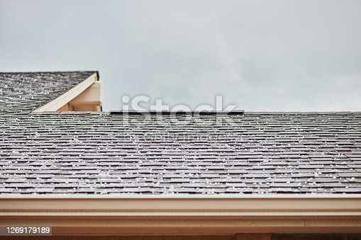 Roof shingles with large hailstones after hail storm