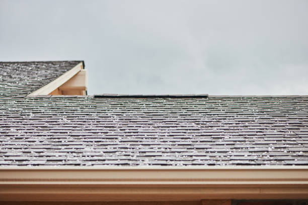 Roof shingles with large hailstones after hail storm stock photo