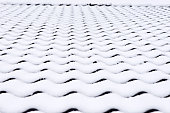 Background of roof tiles covered with snow.