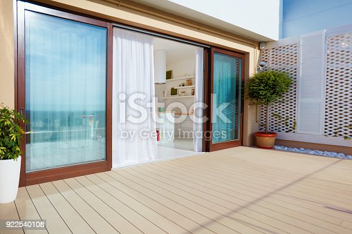 istock roof top patio with open space kitchen, sliding doors and decking on upper floor 922540108
