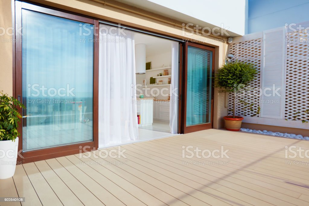 roof top patio with open space kitchen, sliding doors and decking on upper floor stock photo