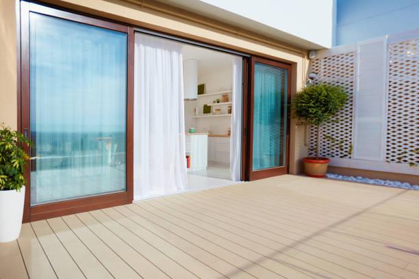オープン スペースのキッチン、引き戸と上の階のデッキと屋根の上パティオ - デッキ ストックフォトと画像