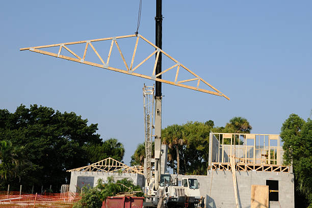 Roof truss being hoisted by crane