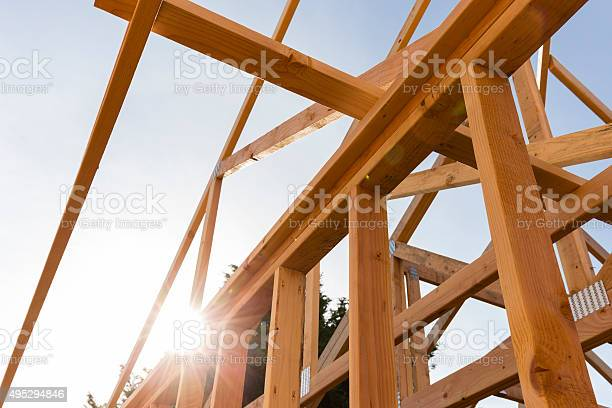 roof trusses of new home construction with blue sky