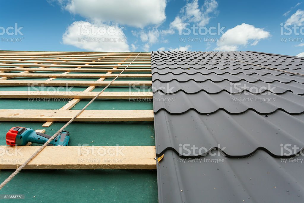 Roof with metal tile,screwdriver and roofing iron stock photo