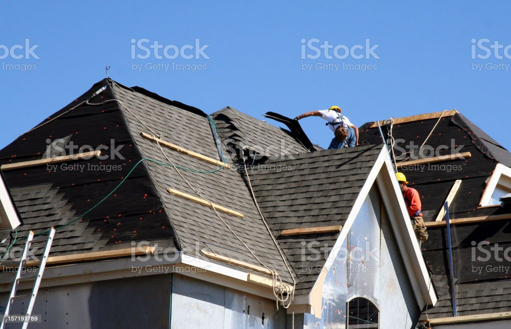 Roof Workers on top of house with blue sky stock photo