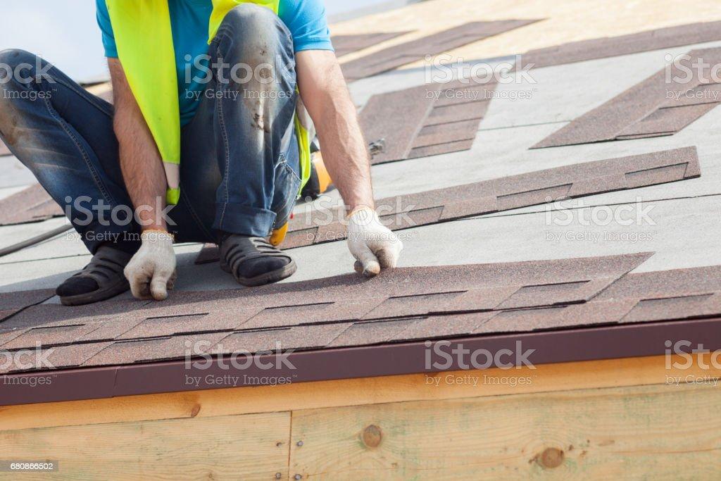Roofer builder worker installing  Asphalt Shingles or Bitumen Tiles on a new house under construction royalty-free stock photo