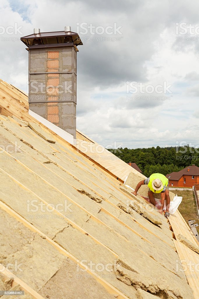 Roofer builder worker installing roof insulation material on new house stock photo