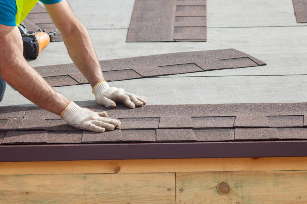 Roofer builder worker installing roof shingles stock photo