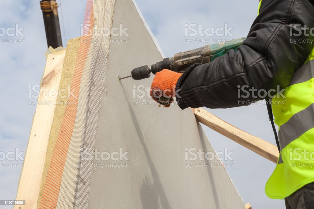 Roofer builder worker use drill to make a hole in structural Insulated Panel stock photo