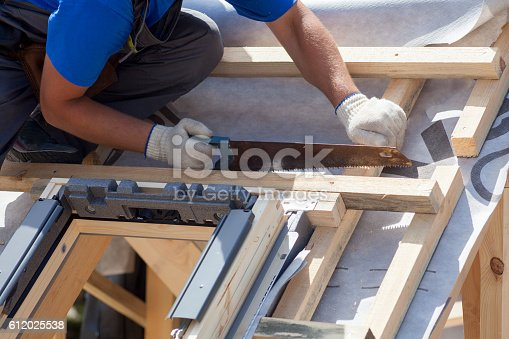 istock Roofer builder worker use saw to cut a wooden beam 612025538