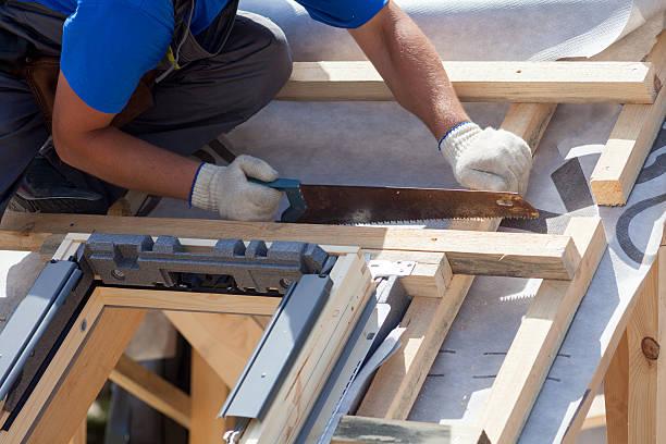 roofer builder worker use saw to cut a wooden beam - fenster einbauen stock-fotos und bilder