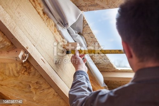 966792200 istock photo Roofer builder worker with ruler install plastic (mansard) or skylight window on attic with environmentally friendly and energy efficient thermal insulation rockwool 1082357740