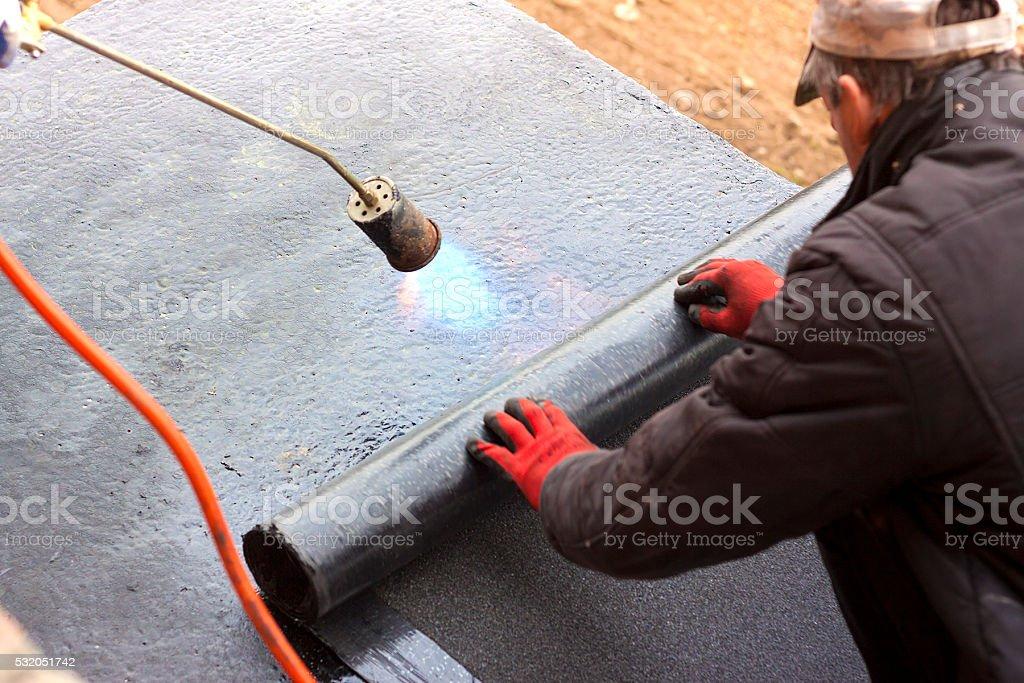 Roofer burning asphalt felts on the garage roof stock photo