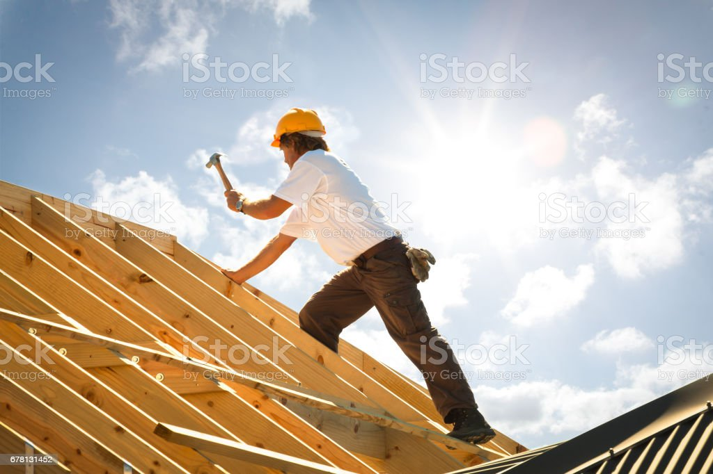 roofer carpenter working on roof ストックフォト