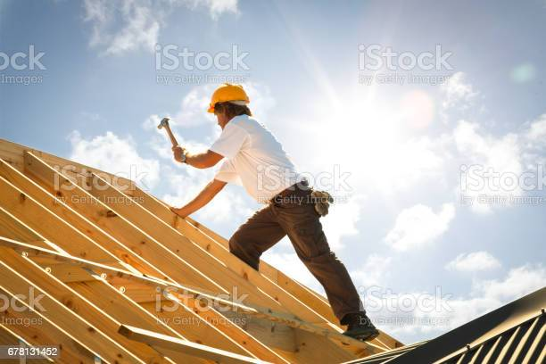 carpenter on roof trusses backlit with sunflare