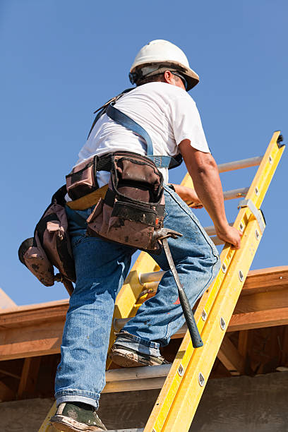 Roofer Climbs Ladder to Get on Top of Home stock photo