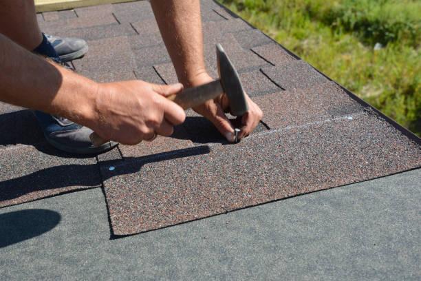 Dakdekker die Asfaltshingles op een dakhoek van de huisbouwmet een hamer en spijkers installeert. Dakbedekking constructie met asfalt shingles. foto