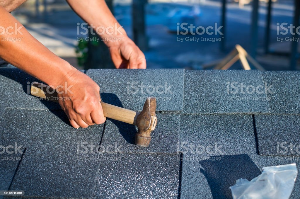 Roofer Installing Corner Bitumen Roof Shingles With Hammer And Nails