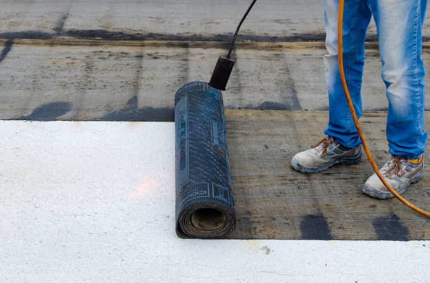 Roofer installing rolls of bituminous waterproofing membrane for the waterproofing of a terrace Roofer installing rolls of bituminous waterproofing membrane for the waterproofing of a terrace waterproof stock pictures, royalty-free photos & images
