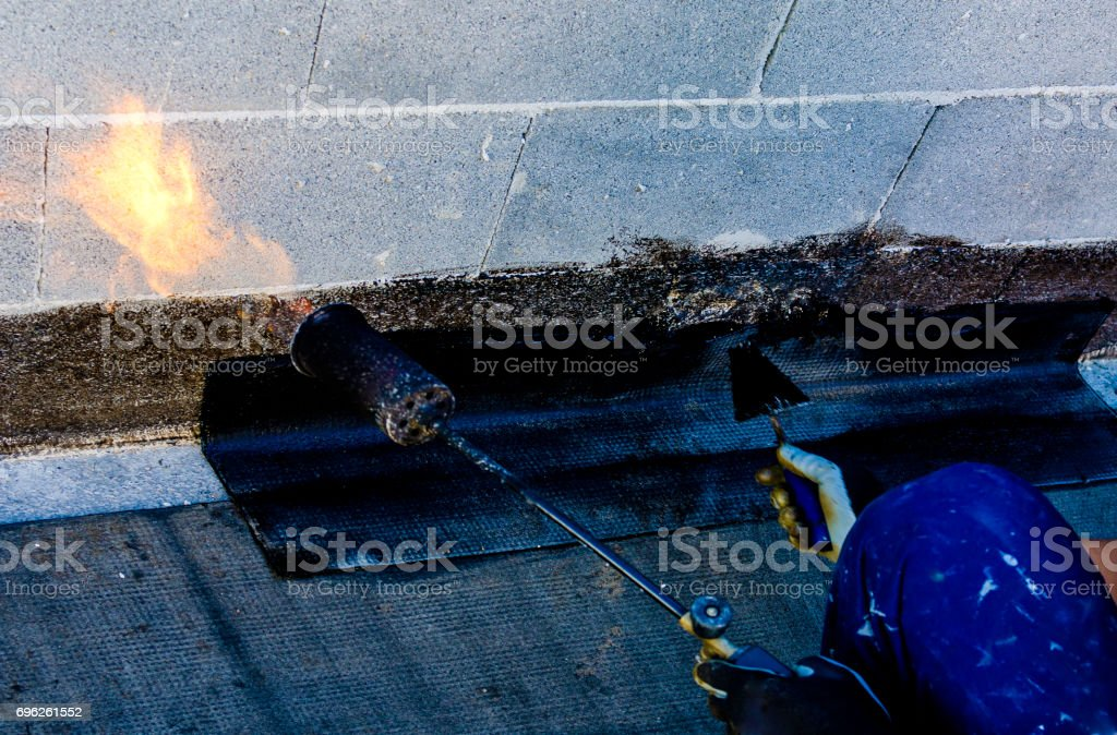 Roofer installing rolls of bituminous waterproofing membrane for the waterproofing of a terrace stock photo