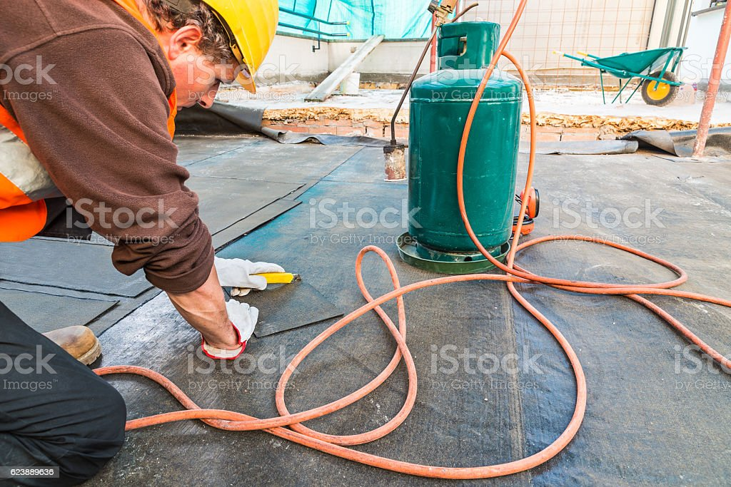 Roofer installing rolls of bituminous waterproofing membrane on a terrace stock photo